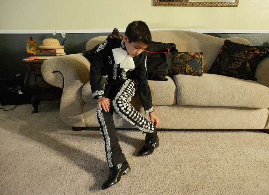 """Sebastien De La Cruz is a young mariachi singer who sang the Star Spangled Banner before the Miami Heat at San Antonio Spurs NBA Championship series game at the AT&T Center on Tuesday. He puts on his boots for a photo shoot at home on June 12, 2013. Sebastien describes himself as a """"proud American."""" Photo: Billy Calzada, San Antonio Express-News / San Antonio Express-News"""