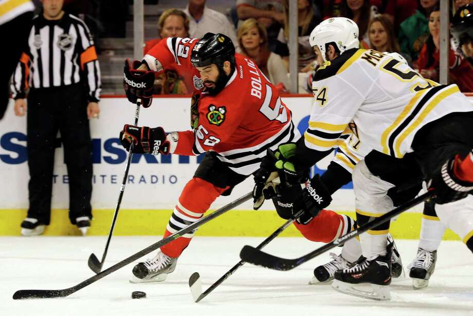 Chicago Blackhawks left wing Brandon Bollig (52) controls the puck against Boston Bruins defenseman Adam McQuaid (54) and Torey Krug during the second period of Game 1 in their NHL Stanley Cup Final hockey series, Wednesday, June 12, 2013, in Chicago. (AP Photo/Nam Y. Huh) Photo: Nam Y. Huh