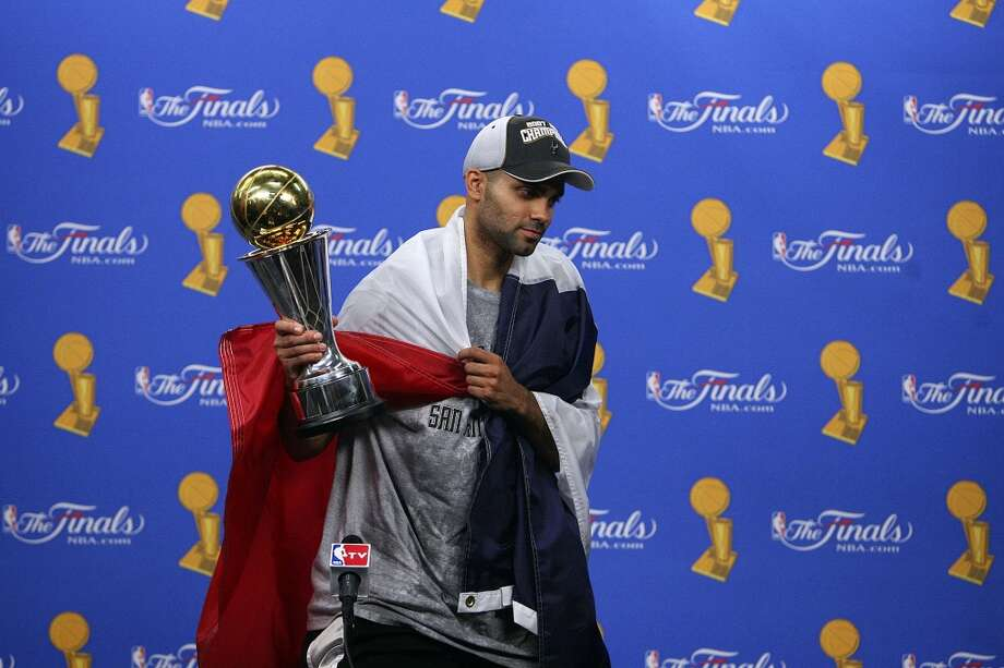 Spurs' guard Tony Parker, of France, (09) holds the MVP trophy while wrapped in a French flag after answering from the media after sweeping the Cavaliers in game 4 in the NBA Finals at the Quicken Loans Arena Thursday June 14, 2007, in Cleveland, OH. (EDWARD A. ORNELAS/STAFF)