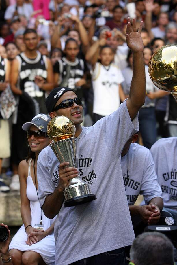 Spurs' guard Tony Parker, of France, (09) holds the MVP thorphy as he waves to fans while his fiancee Eva Longoria takes in the sites during the victory parade Sunday June 17, 2007, at the River Center Lagoon (EDWARD A. ORNELAS/STAFF)