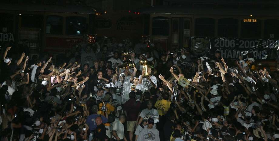 San Antonio Spurs Michael Finley, Tony Parker and Tim Duncan walk to the stage with trophies as they celebrate their fourth NBA Championship title at the Alamodome on Sunday, June, 17, 2007. ( JERRY LARA STAFF )