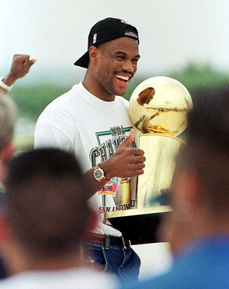 David Robinson of the Spurs carries the NBA championship trophy through the crowd of fans gathered to welcome the team home 26 June, 1999, at San Antonio International Airport. The Spurs defeated the New York Knicks to win the NBA Championship.