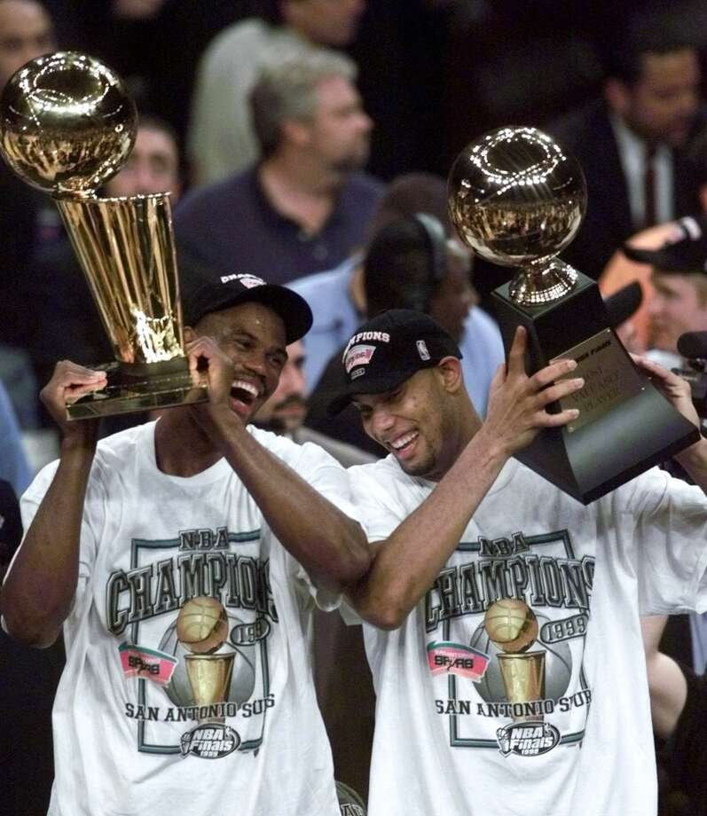 The Spurs' David Robinson (left) holds the NBA championship trophy as teammate Tim Duncan holds the Most Valuable Player trophy after defeating the New York Knicks 78-77 in Game 5 of the 1999 NBA Finals Friday, June 25, 1999, at New York's Madison Square Garden.