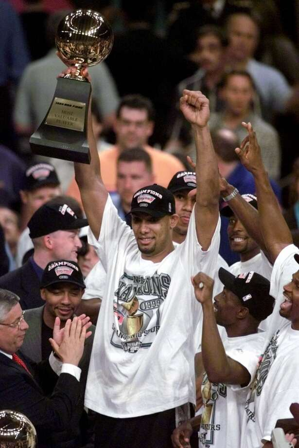 The Spurs' Tim Duncan holds his NBA MVP trophy after the Spurs defeated the New York Knicks 78-77 in Game 5 of the 1999 NBA Finals Friday, June 25, 1999, at New York's Madison Square Garden.