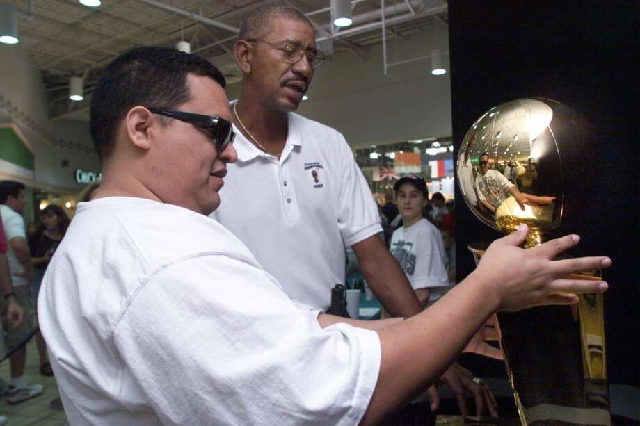 Hall of Famer George Gervin helps Ramiro Martinez to feel the Larry O'Brien Trophy at South Park Mall during a public viewing on Saturday, July 31, 1999. Martinez who is blind was the only person allowed to touch the trophy which the Spurs won last month in the NBA Finals against New York. The trophy tour which started at South Park Mall kicked off a series of public viewings that will be visiting other malls around the city. The Spurs and the city are currently undergoing negotiations for a new arena to be built with public funding. Kin Man Hui/staff.