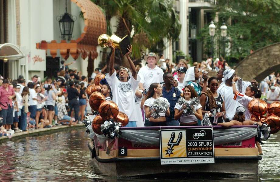 Bruce Bowen holds the 1999 NBA championship trophy at the start of the NBA Championship celebration Wednesday, June 18, 2003, on the San Antonio River.
