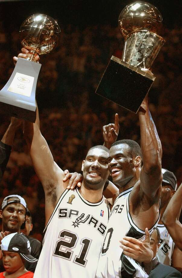 Tim Duncan holds the MVP trophy and David Robinson holds the Larry O'Brien trophy after winning Game 6 of the NBA Finals at the SBC Center in San Antonio on June 15, 2003.