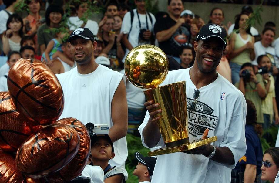 The Spurs' Tim Duncan and David Robinson ride a barge with the 2003 NBA championship trophy during the Spurs Championship river parade on June 18, 2003.