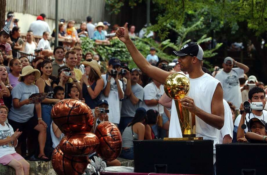 The Spurs' Tim Duncan waves to the crowd while carrying the NBA championship trophy during the San Antonio Spurs Championship river parade on June 18, 2003.