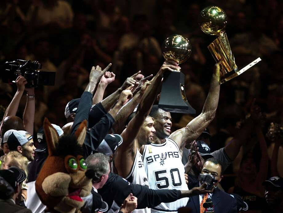 Tim Duncan and David Robinson hold up the hardware as they celebrate Sunday, June 15, 2003 at the SBC Center. The Spurs beat the Nets 88-77 in game 6 to win the NBA Championship.
