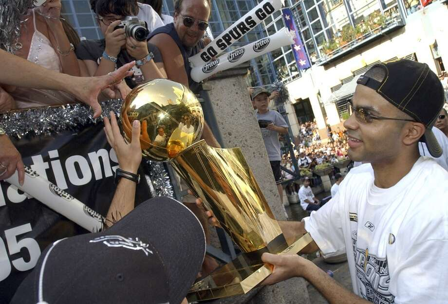 The Spurs' Tony Parker lets fans touch the trophy during the championship parade through the River Center Lagoon Saturday June 25, 2005. FOR PHOTO BY EDWARD A. ORNELAS