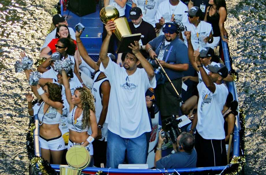Tim Duncan hoists the Larry O'Brien trophy as he rides with teammate Bruce Bowen during the Spurs'  championship parade on June 25, 2005 on the San Antonio River.