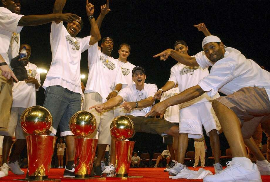Members of the Spurs celebrate with the the three championship trophies during the celebration at the Alamodome on June 25, 2005.
