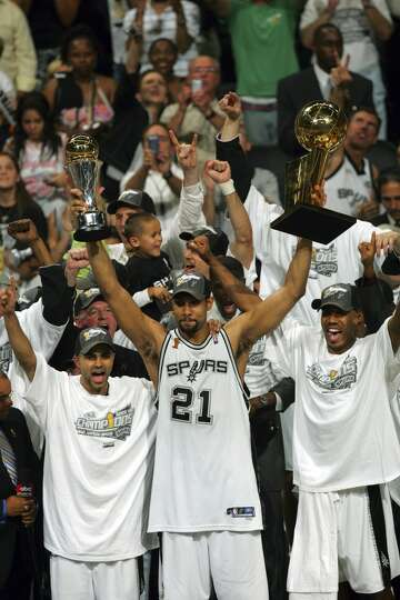 The Spurs' Tony Parker (left), Tim Duncan (with both trophies) and Bruce Bowen celebrate their NBA C