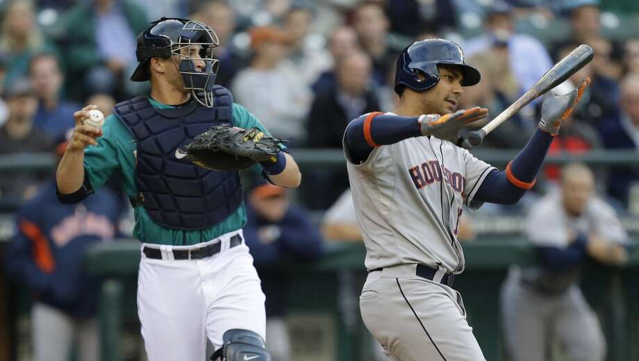 Mariners catcher Mike Zunino, left, returns the ball after Carlos Pena, right, struck out swinging.