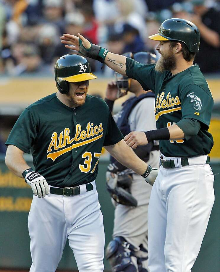 Josh Reddick (right) hands it to Brandon Moss after the first of his two homers. Photo: Carlos Avila Gonzalez, The Chronicle