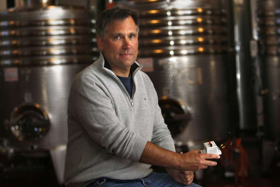 Owner  Jim Mirowski of Treasure Island Wines on Treasure Island in San Francisco, Calif., shows a relay switch that often gets burned out when there is a power loss on Tuesday, June 11, 2013.  The stainless steel fermenting tanks behind him rely on electricity for temperature control.  Residents on Treasure Island were experiencing power loss several times a week last fall.  Jim lost half a ton of grapes he had harvested for making wine during one of last year's power outages.  It has since been fixed but residents say power loss has recently been getting continuously worse.  The city says the power grid is 50 years old and in need of an update.
