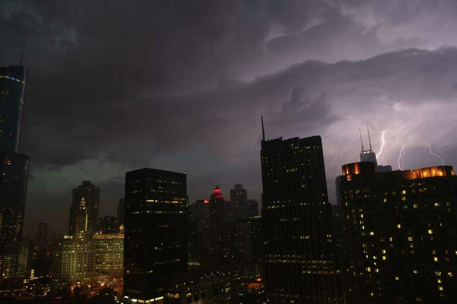 Lightning erupts over downtown Chicago on Wednesday, June 12, 2013, as a line of powerful storms cross over the Midwest. A massive line of storms packing hail, lightning and tree-toppling winds began rolling through the Midwest Wednesday evening and could affect more than one in five Americans from Iowa to Maryland before subsiding. (AP Photo/Dr. Scott M. Lieberman) Photo: Dr. Scott M. Lieberman