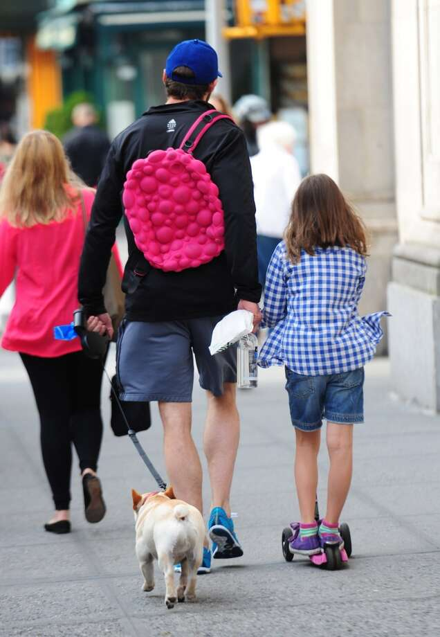 Aww, he even carries daughter Ava's frilly backpack for her.