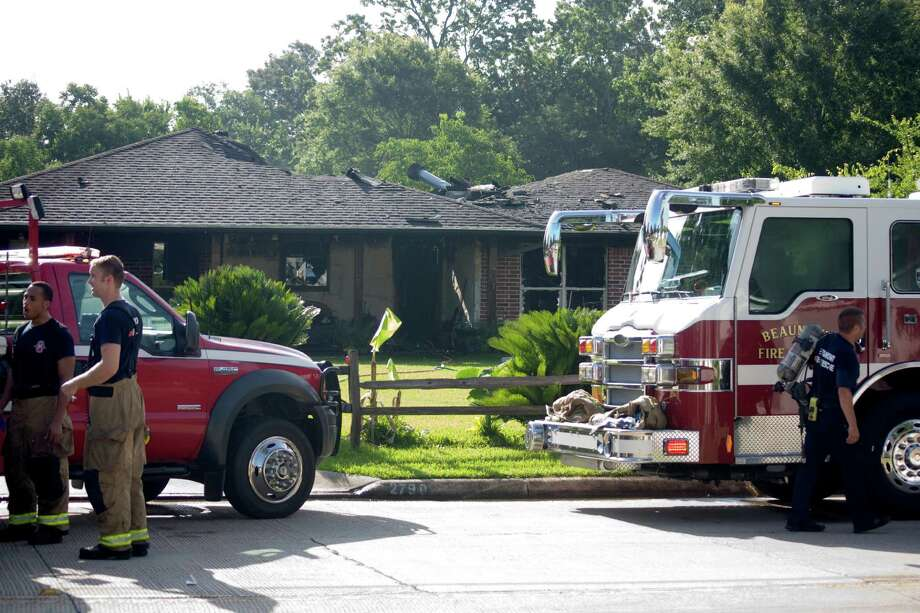 Firefighters worked in the Thursday morning heat to extinguish a fire in the 2,000 block of Lucas Drive. The fire, which injured the homeowner and two firefighters, is being blamed on an electrical short. Photo: Tim Monzingo