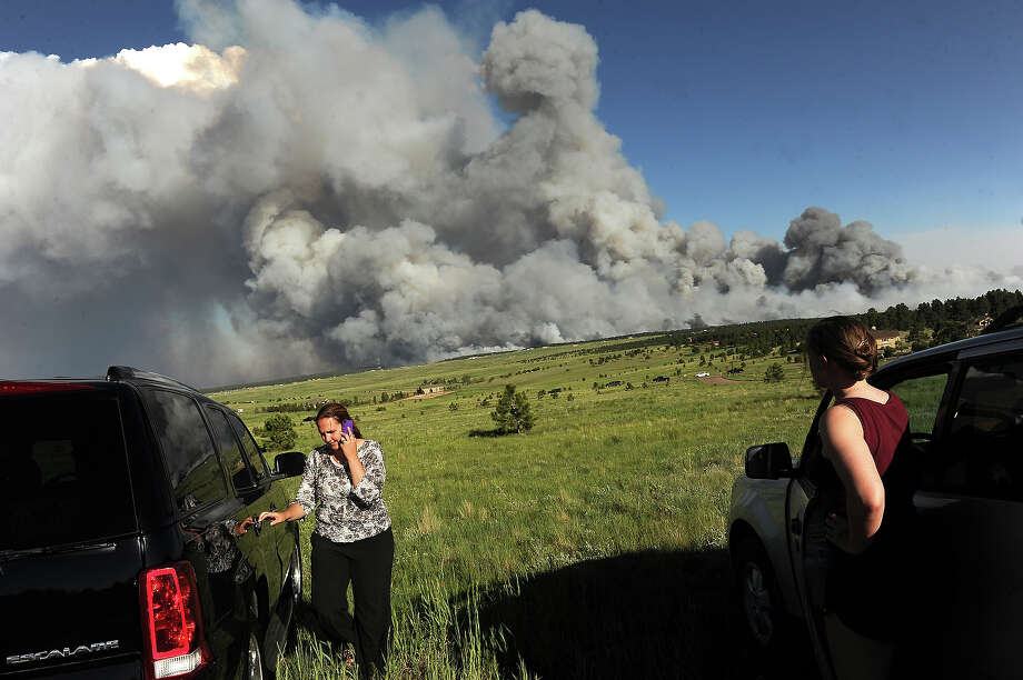 Homeowners watch the fire from a high meadow north of the fire. A wild land fire started around 2:00 in the Black Forest northeast of Colorado Springs, CO on June 11, 2013.  Homes have already burned and the wind is expected to continue through the afternoon. Photo: Helen H. Richardson, Denver Post Via Getty Images / Copyright - 2013 The Denver Post, MediaNews Group.