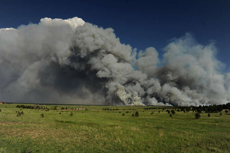 A wall of dark smoke looms large over the horizon as fire destroys the landscape looking south from Mountain Dance Drive and Open Sky Way northeast of  Colorado Srpings, CO on June 11, 2013.  The Black Forest fire started around 1:45 in an area of the Black Forest northeast of Colorado Springs, CO. Homes have already burned and the wind is expected to continue through the afternoon. Photo: Helen H. Richardson, Denver Post Via Getty Images / Copyright - 2013 The Denver Post, MediaNews Group.
