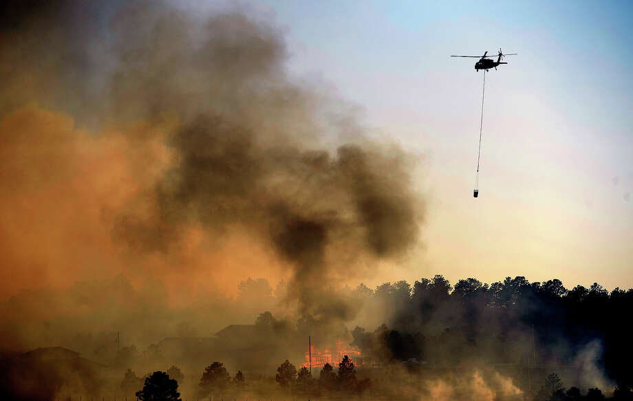 COLORADO SPRINGS, CO - JUNE 11:  A Blackhawk helicopter makes a water drop on a burning structure in the midst of the Black Forest Fire in Colorado Springs, CO on June 11, 2013..  Many homes have already been lost to the raging fire that continues to burn out of control.  Photo by Helen H. Richardson/The Denver Post via Getty Images) Photo: Helen H. Richardson, Denver Post Via Getty Images / Copyright - 2013 The Denver Post, MediaNews Group.