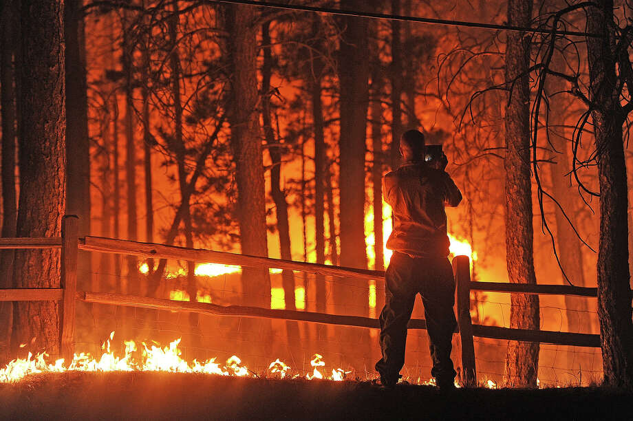 A Denver Post photographer shoots video of a house burning late in the evening along Swan Road in the Black Forest northeast of Colorado Springs, CO on June 11, 2013. Photo: Helen H. Richardson, Denver Post Via Getty Images / Copyright - 2013 The Denver Post, MediaNews Group.