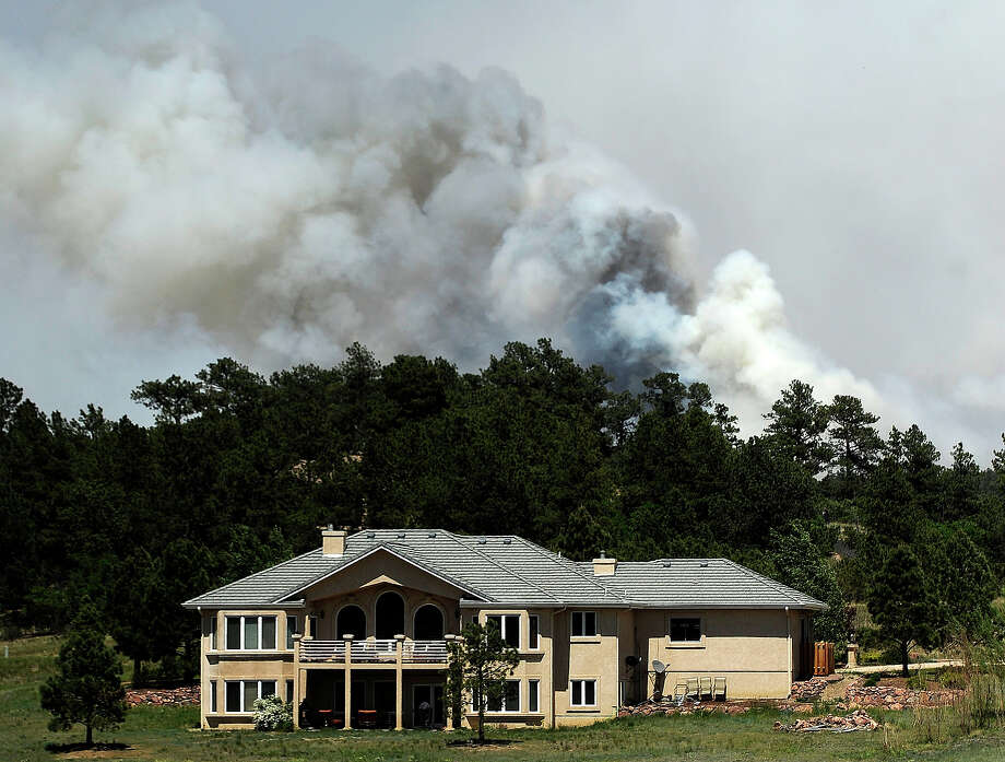 Smoke billows near a home from the Black Forest Fire on June 12, 2013 north of Colorado Springs, Colorado. The fire has reportedly burned 80 to 100 homes and has charred at least 8,000 acres. Photo: Chris Schneider, Getty Images / 2013 Getty Images