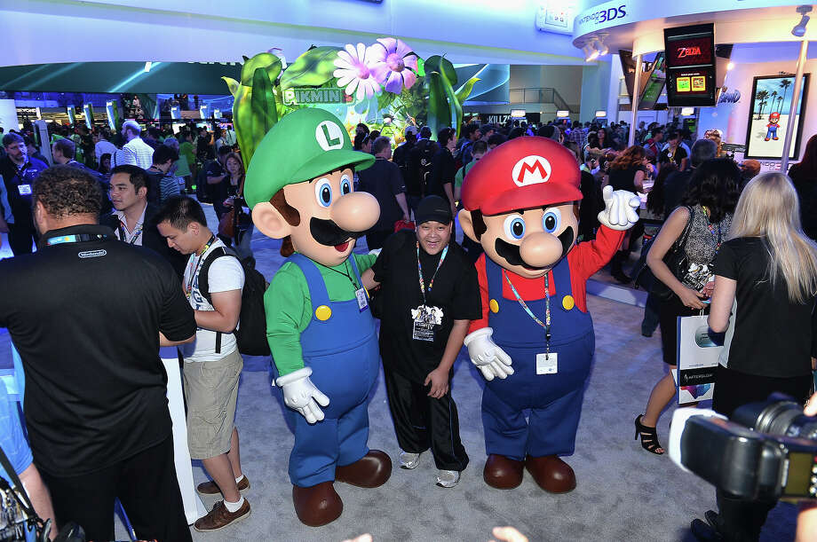 A fan poses with the Super Mario Brothers at the E3 Gaming and Technology Conference at the Los Angeles Convention Center on June 11, 2013 in Los Angeles, California. Photo: Alberto E. Rodriguez, Getty Images / 2013 Getty Images