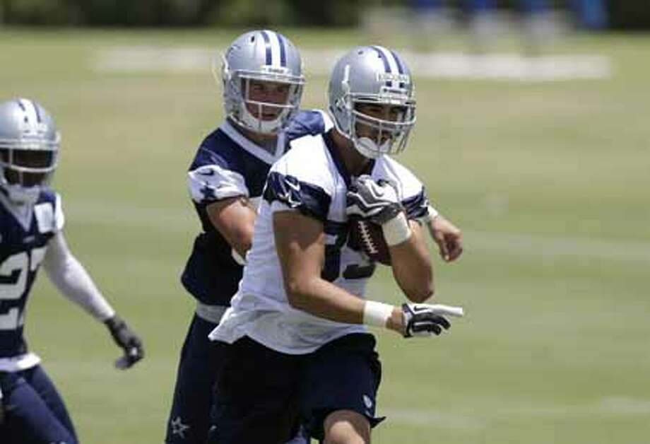 Dallas Cowboys tight end Gavin Escobar (89) runs through defenders after grabbing a pass during their NFL football minicamp on Wednesday, June 12, 2013, in Irving, Texas. (AP Photo/Tony Gutierrez) Photo: Tony Gutierrez, Associated Press / AP