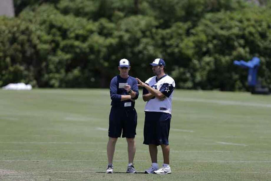 Dallas Cowboys head coach Jason Garrett, left, talks with quarterback Tony Romo as they watch the team run drills during their NFL football minicamp on Wednesday, June 12, 2013, in Irving, Texas. (AP Photo/Tony Gutierrez) Photo: Tony Gutierrez, Associated Press / AP