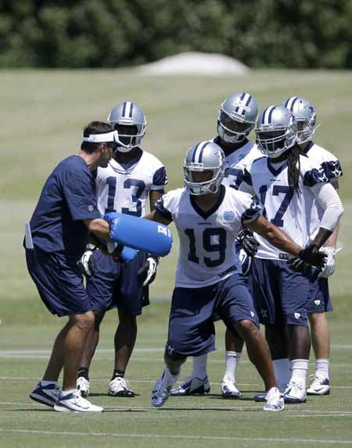 Dallas Cowboys wide receivers coach  Derek Dooley works out with Miles Austin (19) as the team runs drills during their NFL football minicamp on Tuesday, June 11, 2013, in Irving, Texas. (AP Photo/Tony Gutierrez) Photo: Tony Gutierrez, Associated Press / AP