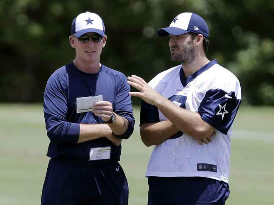 CORRECTS DATE - Dallas Cowboys head coach Jason Garrett, left, talks with quarterback Tony Romo as the two watch the team participate in drills during NFL football minicamp on Wednesday, June 12, 2013, in Irving, Texas. (AP Photo/Tony Gutierrez) Photo: Tony Gutierrez, Associated Press / AP