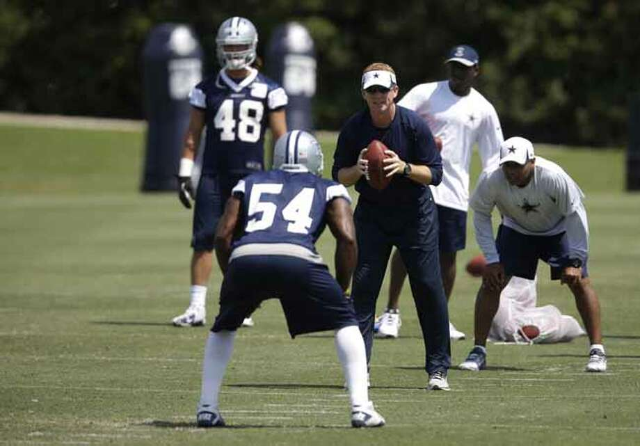 Dallas Cowboys head coach Jason Garrett runs drills as linebacker Bruce Carter (54) and Cameron Lawrence (48) watch during an organized team activity Tuesday, June 4, 2013, in Irving, Texas. (AP Photo/Tony Gutierrez) Photo: Tony Gutierrez, Associated Press / AP