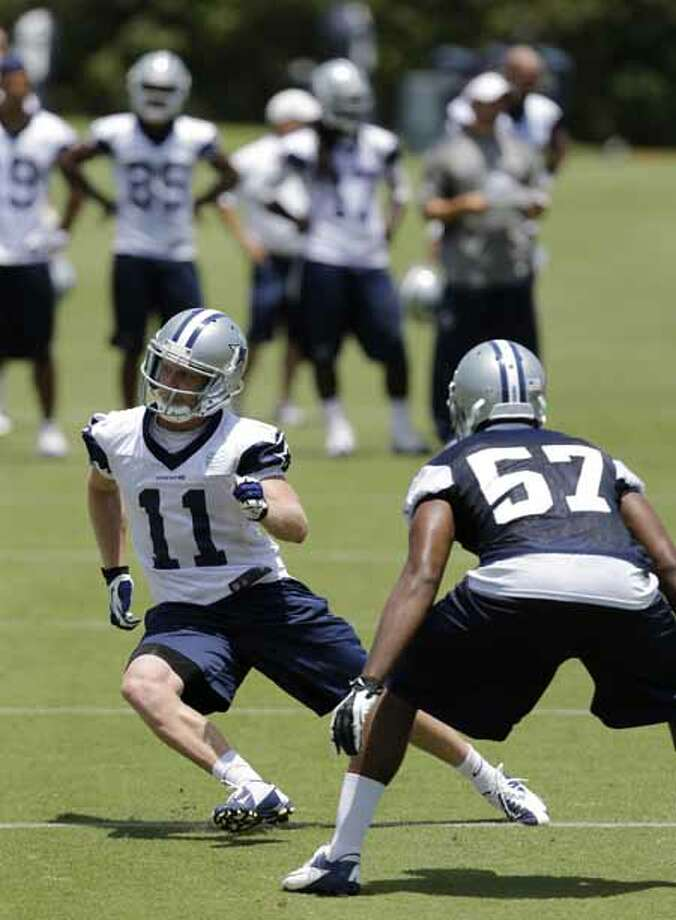 Dallas Cowboys wide receiver Cole Beasley (11) runs a route against linebacker DeVonte Holloman (57) as the team runs a play during their NFL football minicamp on Wednesday, June 12, 2013, in Irving, Texas. (AP Photo/Tony Gutierrez) Photo: Tony Gutierrez, Associated Press / AP