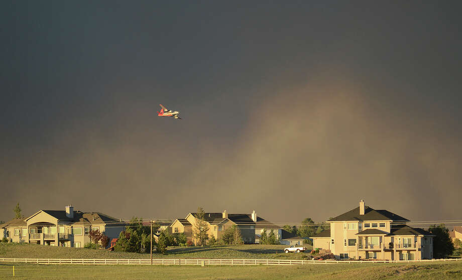 A slurry bomber flies over homes as it prepares to drop fire retardant on the Black Forest Fire in northeast of Colorado Springs on Tuesday, June 11, 2013. The fire consumed an estimated 7500 acres. It damaged 40-60 structures and forced the evacuation of thousands of people. As of Tuesday night the fire was reported as zero percent contained. (AP Photo/BryanOller) Photo: Bryan Oller, ASSOCIATED PRESS / THE ASSOCIATED PRESS2013