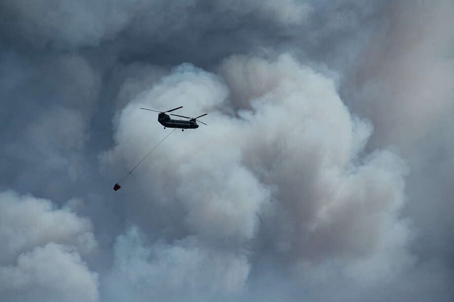 A Chinook helicopter passes in front of clouds of smoke from the Black Forest fire burning northeast of Colorado Springs, Colo. Wednesday, Jun 12, 2013. A pair of U.S. Defense Department cargo planes was mobilized Wednesday to help battle wildfires in Colorado and elsewhere in the West as crews surveyed the damage from a large blaze burning near Colorado Springs that already has destroyed dozens of homes.  (AP Photo/The Colorado Springs Gazette, Mark Reis) MAGS OUT Photo: Mark Reis, ASSOCIATED PRESS / AP2013