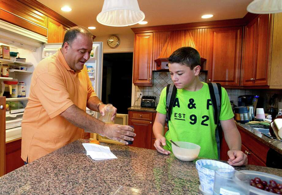 Dominick Bria helps his son, Jason, get ready for school in their Stamford home on Thursday, June 13, 2013. Photo: Lindsay Perry / Stamford Advocate