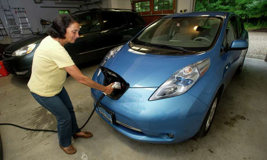 Etta Kantor unplugs her Nissan Leaf in New Canaan on Thursday, June 13, 2013. Photo: Lindsay Perry / Stamford Advocate
