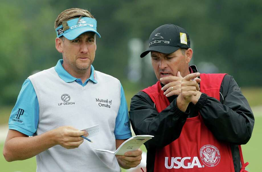 Ian Poulter, left, of England, talks with caddie Terry Mundy before teeing off on the 14th hole after a weather delay during the first round of the U.S. Open golf tournament at Merion Golf Club, Thursday, June 13, 2013, in Ardmore, Pa. (AP Photo/Charlie Riedel) Photo: Charlie Riedel, Associated Press / AP