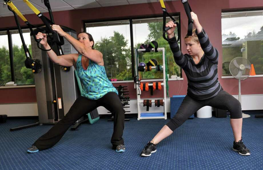 Carin Newman, 45, of Newtown, left, works with trainer Katie Olejniczak on Total Body Resistance exercises, or TRX, Thursday, June 13, 2013. Katie Olejniczak, 25, of New Milford, is the manager and TRX trainer at the medical fitness center at Associated Neurologists in Danbury, Conn. Photo: Carol Kaliff / The News-Times