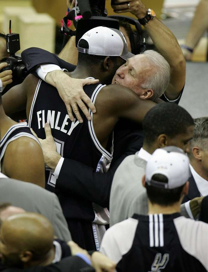 Spurs coach Gregg Popovich and Michael Finley embrace following the Spurs' win in the NBA Finals Game 4. It was the first title for Finley.
