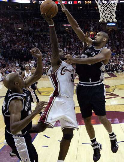 The Spurs' Tim Duncan defends Cavaliers' LeBron James as Bruce Bowen looks on during second half act