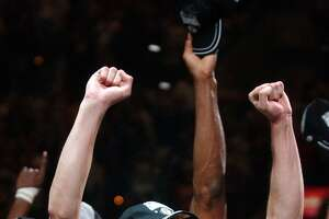The Spurs' Manu Ginobili celebrates his first NBA title with the rest of the team after defeating the Nets in Game 6 of the 2003 NBA Finals to capture the team's second championship title at the SBC Center.