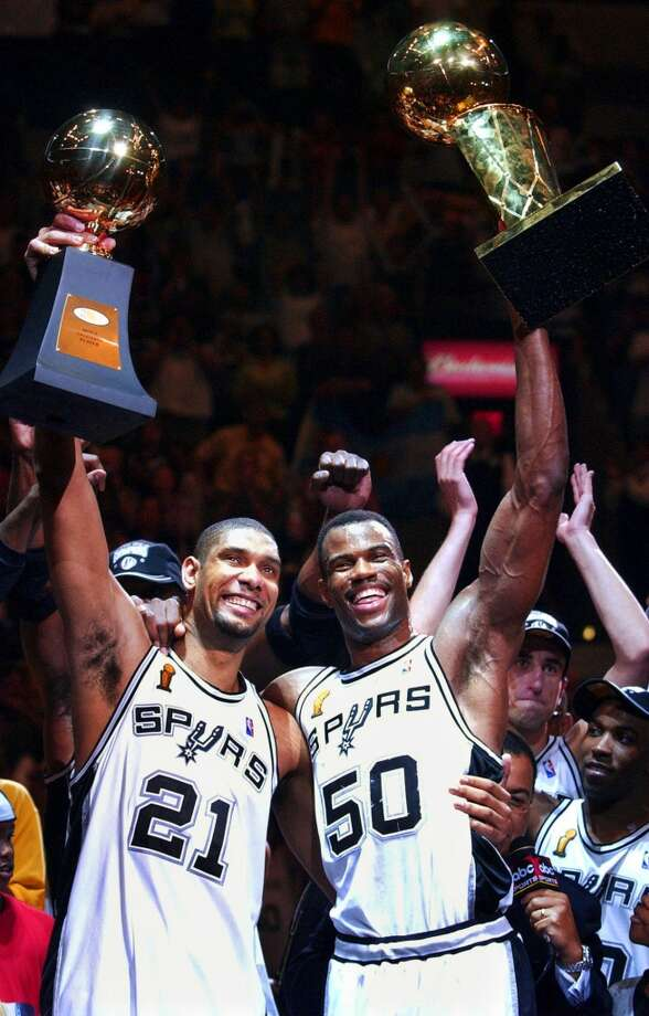 Spurs players Tim Duncan (21) holds his MVP trophy while teammate David Robinson (50) holds the championship trophy after the Spurs beat the New Jersey Nets 88-77 to win the NBA Championship in Game 6 of the NBA Finals in San Antonio, June 15, 2003. It was Robinson's final season and he went out a champion.