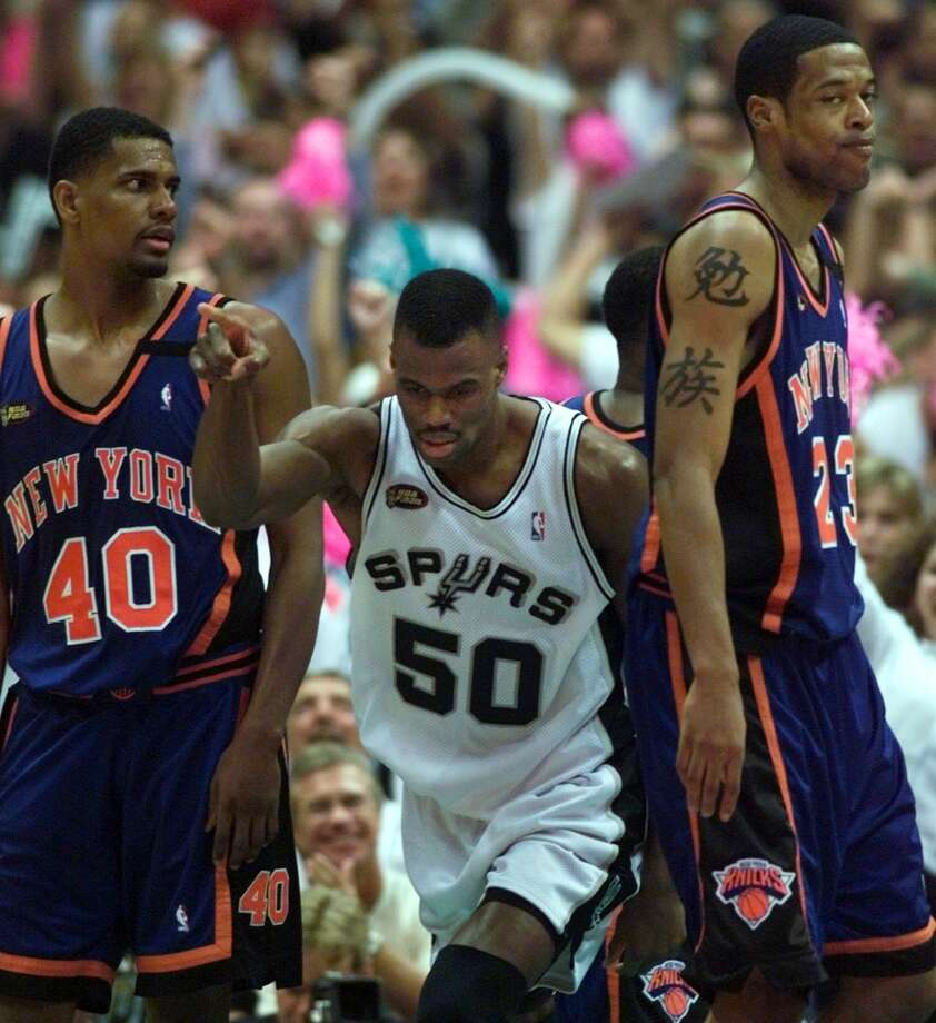 David Robinson celebrates near the end of Game 2 of the NBA on Friday June 18, 1999 at the Alamodome. A dejected Marcus Camby, right, and Kurt Thomas look on.
