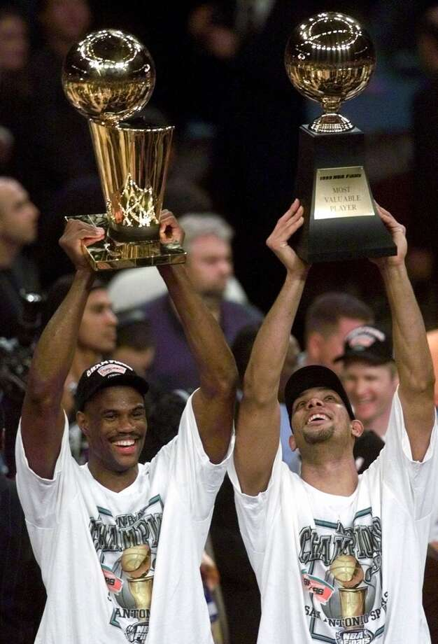 The Spurs' David Robinson, left, holds up the NBA Championship trophy as teammate Tim Duncan holds up the Most Valuable Player trophy after defeating the New York Knicks 78-77 in Game 5 of the 1999 NBA Finals Friday, June 25, 1999, at New York's Madison Square Garden.