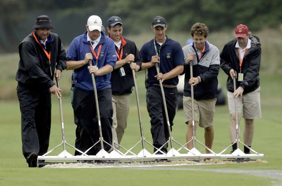 Course workers clear water from the sixth fairway after a weather delay during the first round of the U.S. Open golf tournament at Merion Golf Club, Thursday, June 13, 2013, in Ardmore, Pa. (AP Photo/Julio Cortez)
