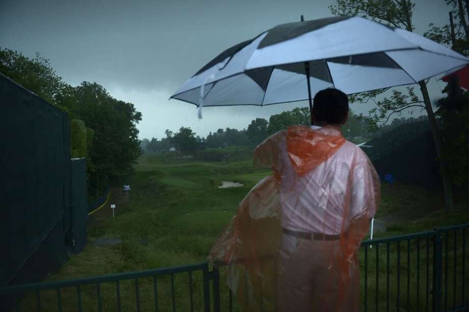 A man looks out over the 18th hole after play was suspended during a storm at the first round the US Open at Merion Golf Club June 13, 2013 in Ardmore, Pennsylvania. AFP PHOTO/Brendan SMIALOWSKIBRENDAN SMIALOWSKI/AFP/Getty Images